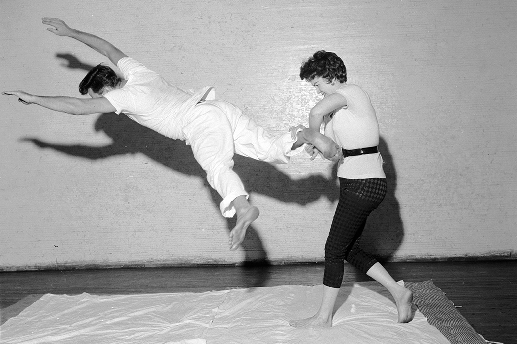 At a self-defence demonstration a woman uses a judo heel and leg turnover against a kicking attacker.