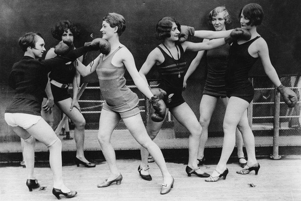 Photograph: Female referees look on as two pairs of young women simulate boxing in a ring, 1931.