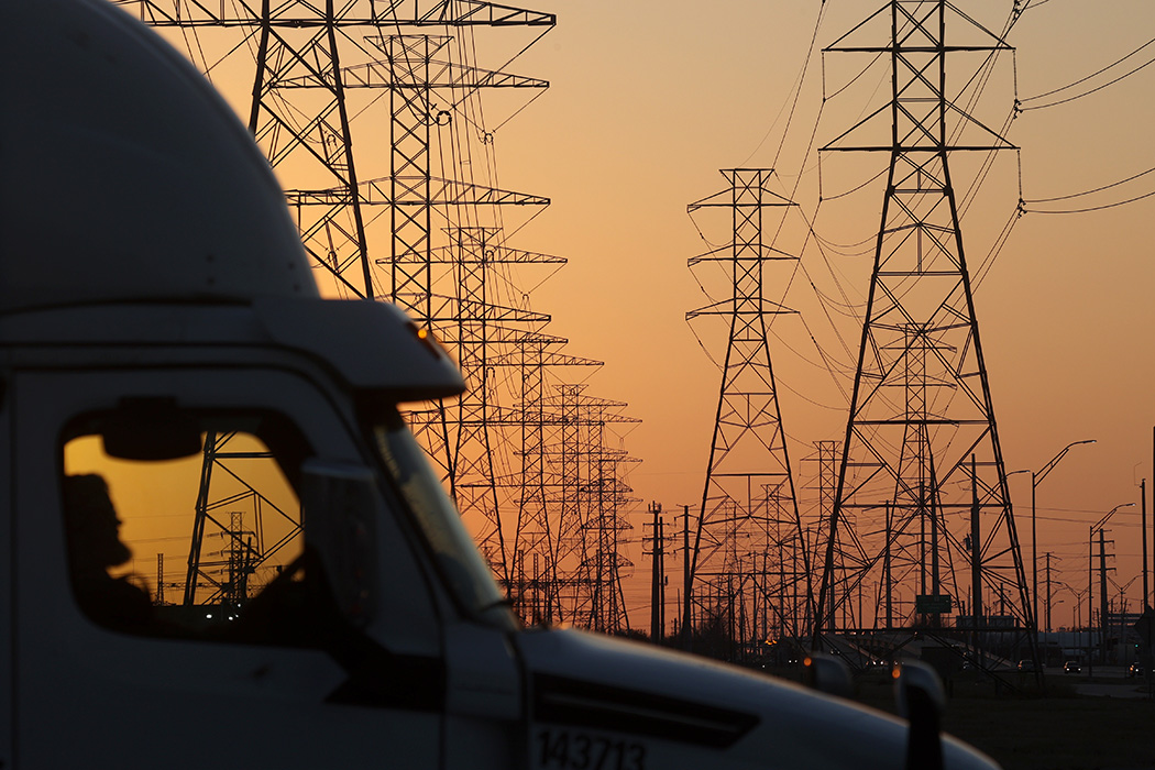 A truck passes a row of high voltage transmission towers on February 21, 2021 in Houston, Texas.