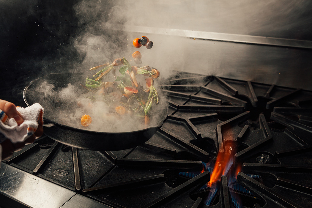 Vegetables cooking in a pan on a stove