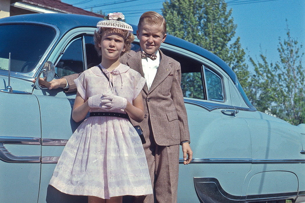 Boy and girl standing in front of camera with car.