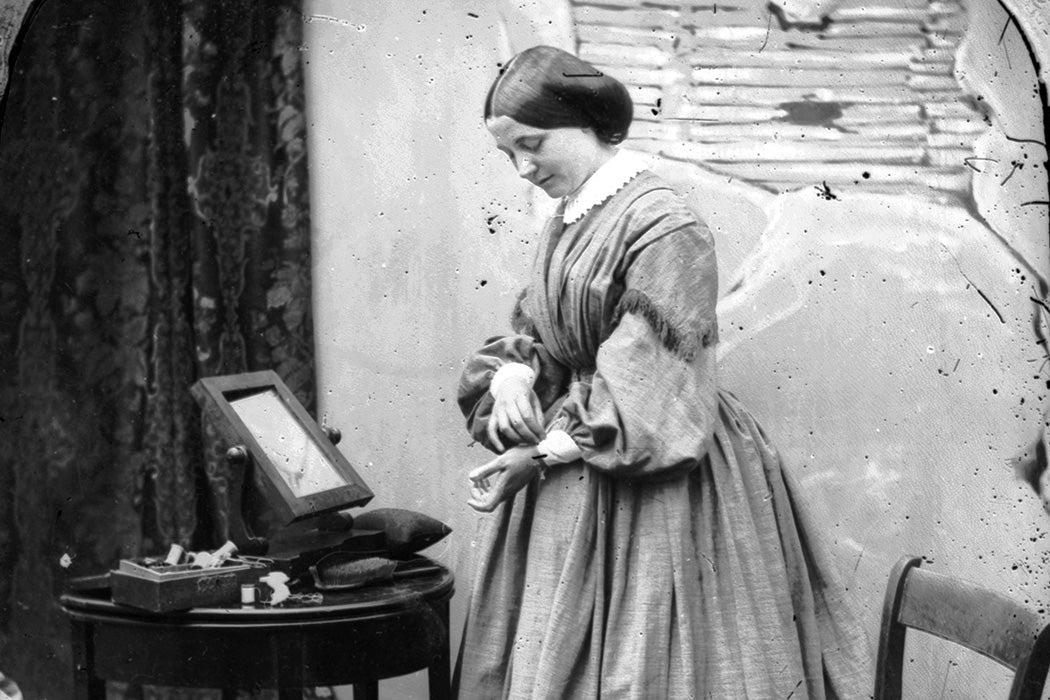 : A woman adjusting her dress, London, c. 1865