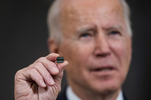 President Joe Biden holds a semiconductor during his remarks before signing an Executive Order on the economy