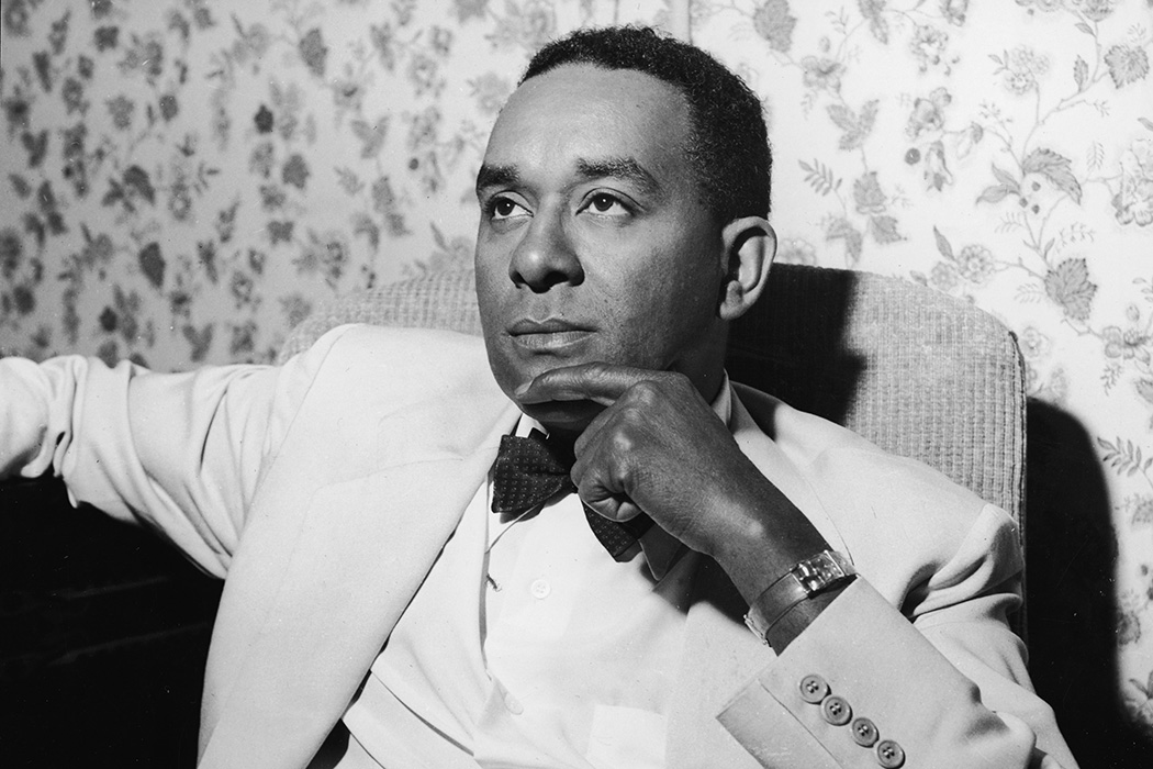 Richard Wright sits in an armchair with his hand to his chin, 1950s.
