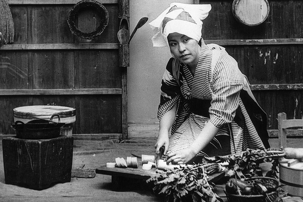 A Japanese woman cuts up radishes in her kitchen