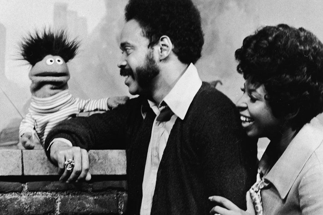 Matt Robinson (as Gordon) and Loretta Long (as Susan) lean on a brick wall and speak with Roosevelt Franklin, 1970