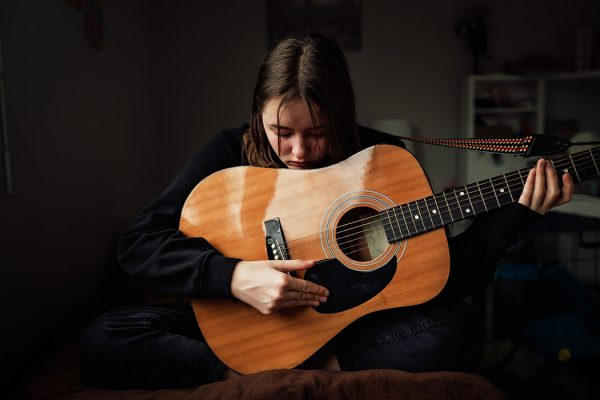 Depressed teen girl in black clothes playing guitar sitting on bed in her room.