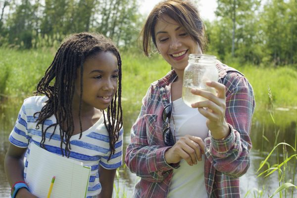 A teacher is standing next to a young student examining her findings from the pond.