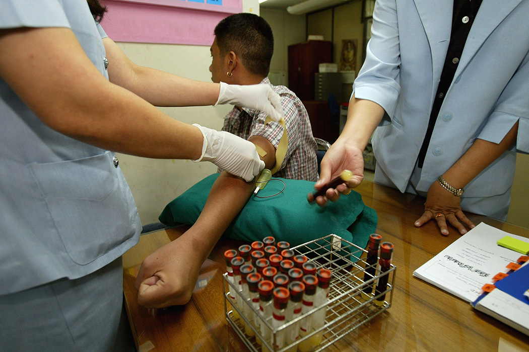 Nurses withdraw blood for testing from a volunteer taking part in the AIDSVAX B/E vaccine trial July 18, 2002 at the Boon Mee Clinic in Bangkok, Thailand.