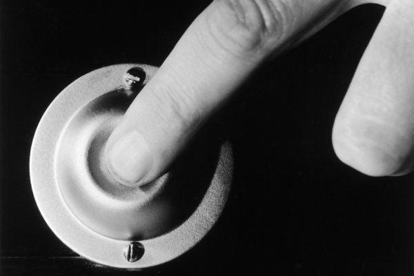 A finger pressing a doorbell, circa 1950.