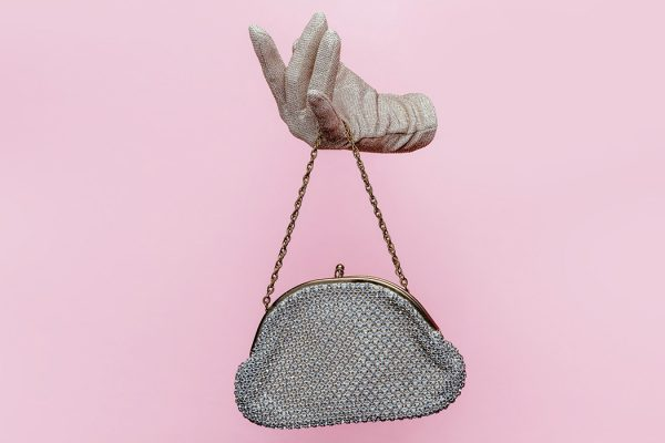 Studio photograph of Floating gloved hand holding purse on pink background.
