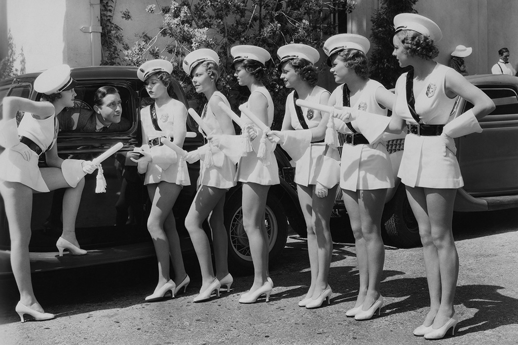 Actor John Boles with extras from his latest musical, 'Redheads On Parade', 1935