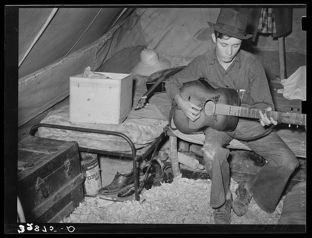 White migrant strawberry picker playing guitar in his tent near Hammond, Louisiana