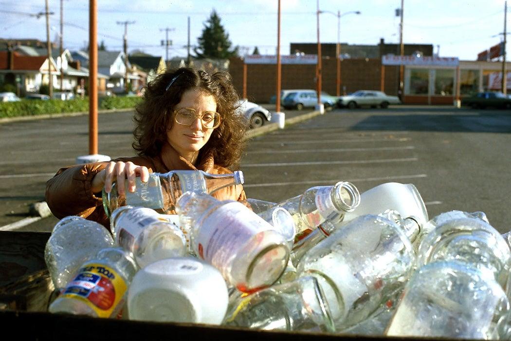 Woman recycling glass, Wallingford neighborhood, Seattle, Washington, 1990