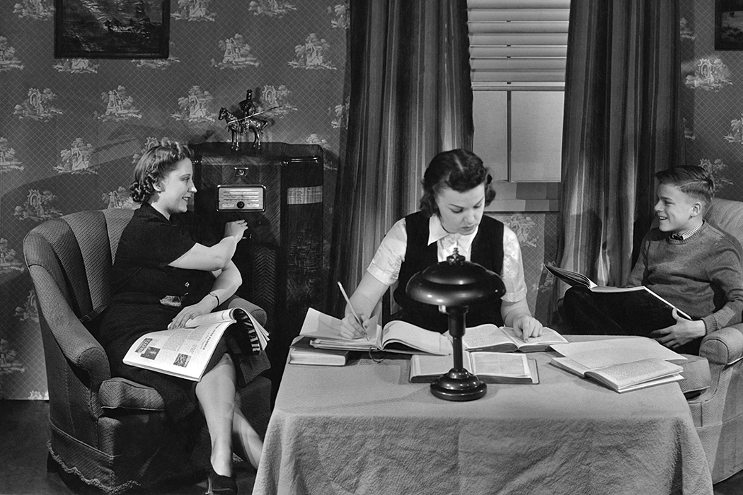 A girl and boy doing homework as a woman listens to the radio in the 1940's