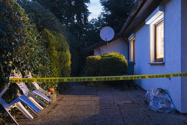 Police tape across a driveway