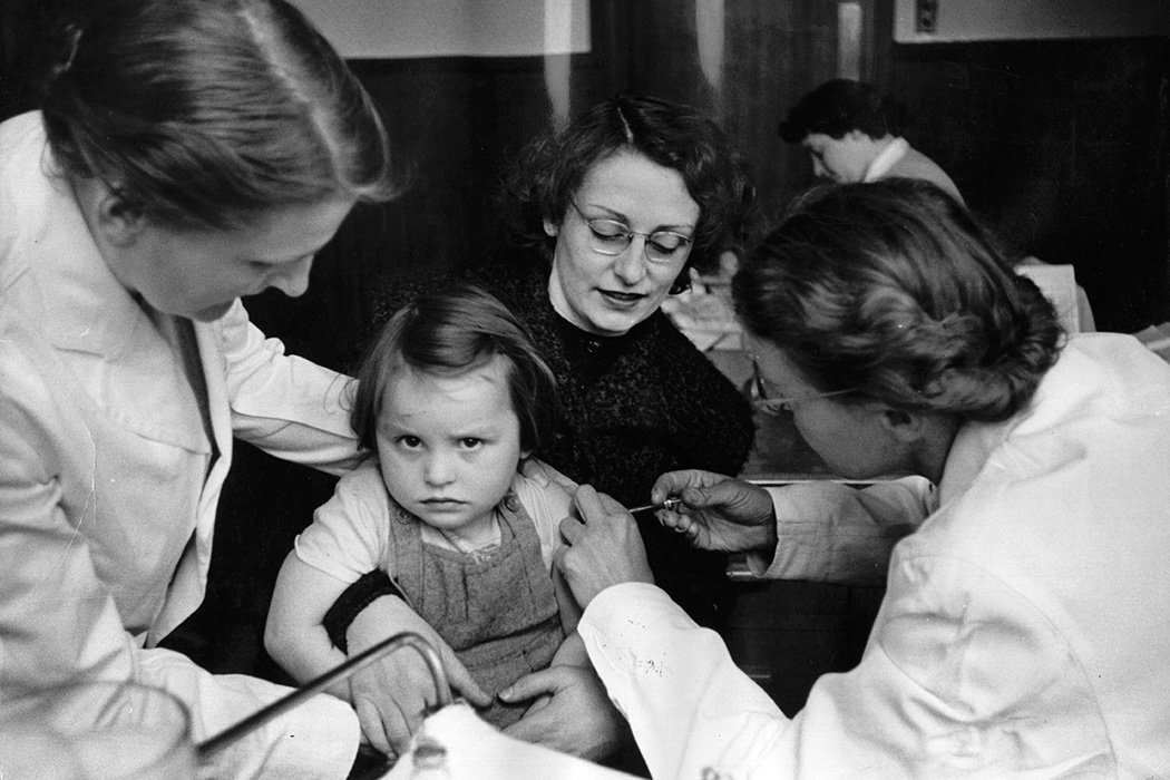 A rather reluctant-looking girl is given an injection of vaccine