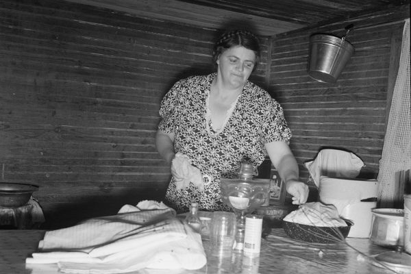 Tobacco sharecropper's wife cleaning up table after washing breakfast dishes. Person County, North Carolina, 1939, by Dorothea Lange