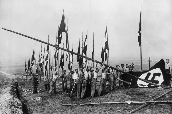 Barechested workers erect a Nazi flag on a hill at Buckeberg in preparation for a Harvest Festival.